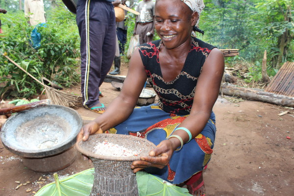 A woman from Bokumu Mokola demonstrates how to make a corn flour.