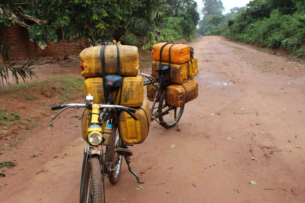 Because of poor road maintenance and the high cost of vehicles, bicycles are often the main source of transport from the village to the city. These bicycles are stacked high with palm oil, which will hopefully fetch a higher price closer to the city.